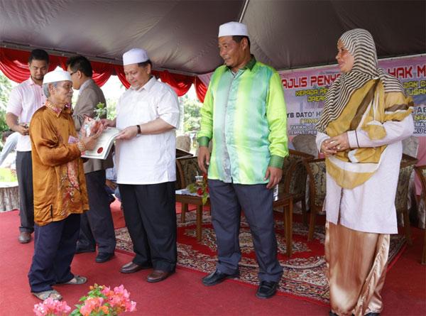 Mohd Amar menyampaiakan geran tanah kepada peneroka di Felda Chiku 2