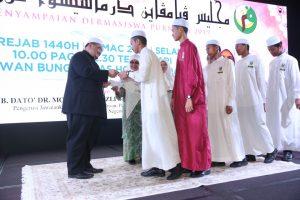 Dr Fadzli Hassan menyampaikan dermasiswa kepada pelajar.