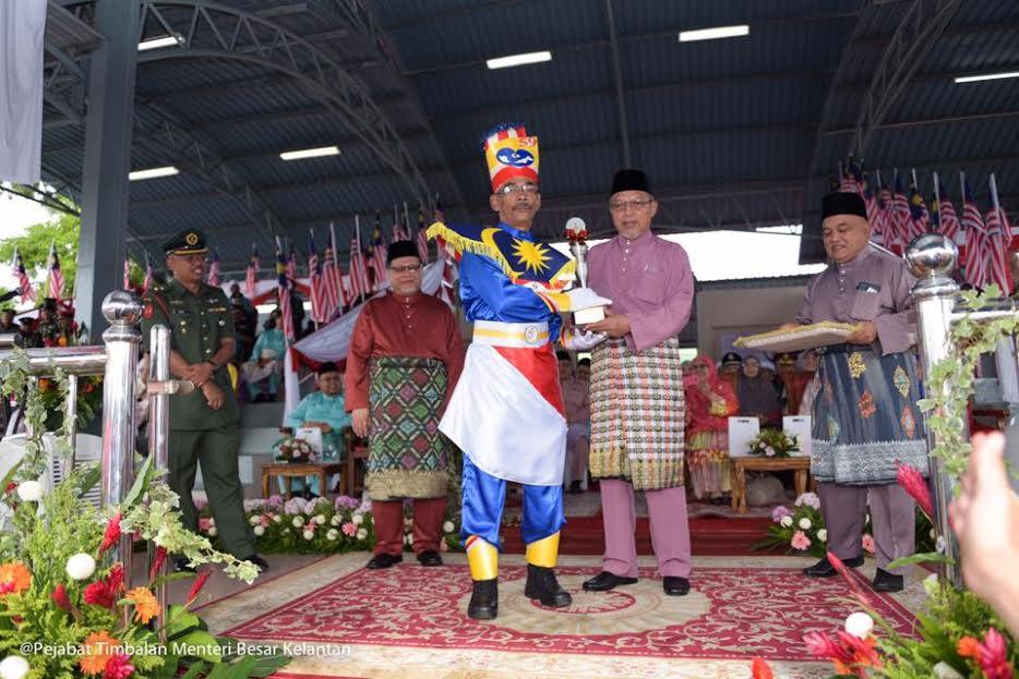 Ustaz Ahmad menyampaikan hadiah kepada wakil kontijen Majlis Perbandaran Kota Bharu Bandaraya Islam (MPKB-BRI) yang memenangi perbarisan terbaik perarakan kemerdekaan.