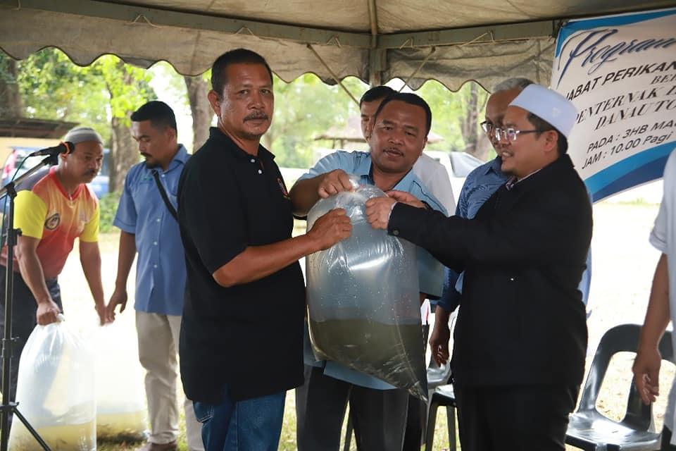 Ustaz Tuan Saripudin Tuan Ismail menyerah benih ikan kepada penternak